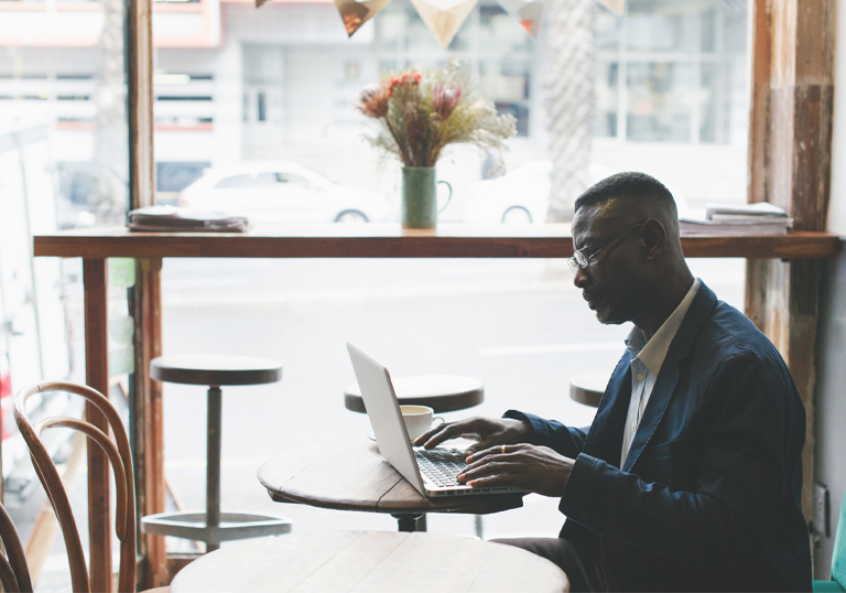 Gentleman using his laptop in a café to research online lending reviews